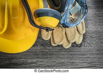 Protective leather gloves goggles earmuffs hard hat on wood board
