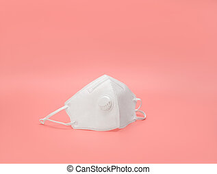 Protective medical mask on a pink background. Respirator with filter. Protection and prevention against coronavirus, covid-19 and other viruses.