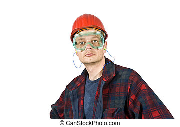 A construction worker wearing protective work wear for safety: a hard top, ear plugs and goggles.