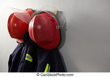 Close-up of protective workwear and hard hat hanging on hook