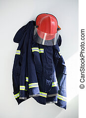 Close-up of protective workwear hanging against white wall