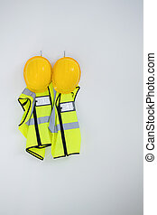 Protective workwear hanging on hook against white background