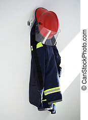 Protective workwear hanging on hook against white wall