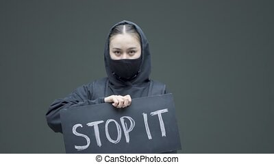 Protesting angry girl in black mask holding cardboard sign with inscription stop it on gray studio background