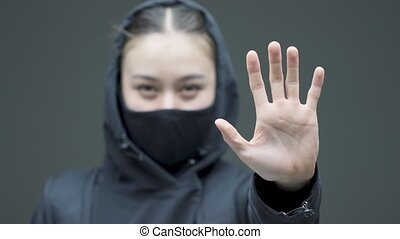Protesting woman activist in black mask and hood show stop gesture on gray studio background, close up. High quality 4k footage