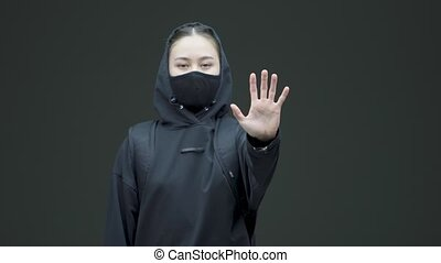 Protesting woman feminist in black mask and hoodie show stop gesture to gender discrimination on gray studio background. High quality 4k footage