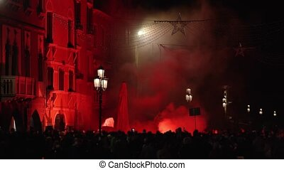 Silhouettes of protestors with waving flag and sign watch rising smoke cloud illuminated by red light on Chioggia street at night
