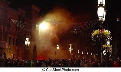 Protestors against virus lock-down stand with Italian flag by pillar of orange smoke on Little Venice city street at night