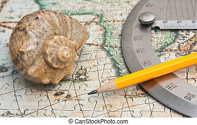protractor and seashell on the map