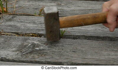 protruding nails hammer in a sledgehammer, slow motion
