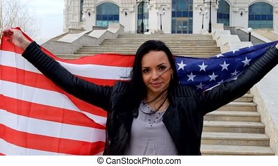 Proud american girl holding stars and stripes flag outdoors....