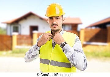 Proud and confident architect or constructor standing in front of new house