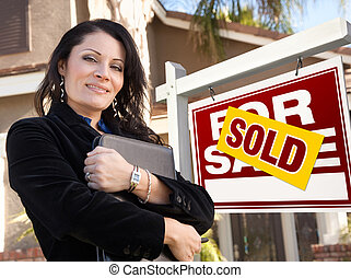 Proud, Attractive Hispanic Female Agent In Front of Sold For Sale Real Estate Sign and House.