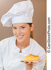 Proud bakery worker holding a slice of flan
