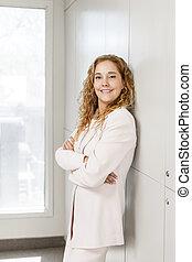 Proud businesswoman standing in hallway
