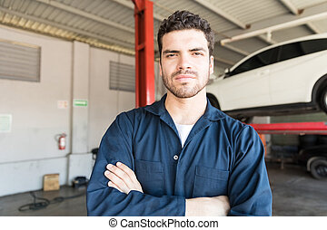 Proud Car Technician In Coveralls Standing At Garage