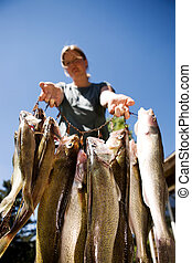Proud Catch - A group of freshly caught fish being held up...