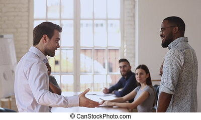 Proud Caucasian manager boss handshaking congratulating praising male black African worker give positive feedback supporting promising reward promoting at team meeting, employee recognition concept