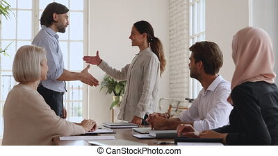 Proud male company executive manager shake hand of happy female employee intern praise young worker congratulate with promotion, appreciate employee for professional achievement, staff reward concept