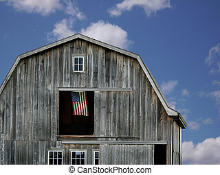 Proud Country - An American flag flying in a barn hayloft.