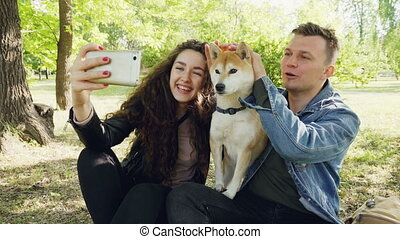 Proud dog owners happy couple are taking selfie with...