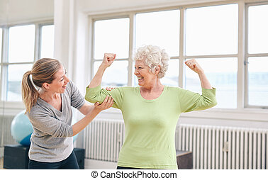 Proud elderly woman flexing her bicep with personal trainer