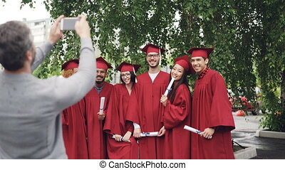 Proud father is taking pictures of graduating students with...