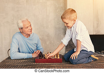 Proud grandfather watching grandson make move with pawn