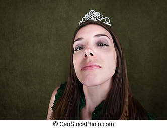 Proud woman with tiara on green background
