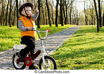 Proud little boy boy with his bike standing on a paved path through a wooded park pointing his finger into the distance