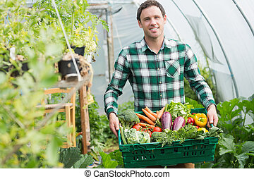 Proud man presenting vegetables in a basket standing...