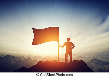 Proud man raising a flag on the peak of the mountain. Challenge, achievement