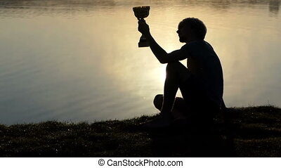 Proud man sits on a lake bank and looks at a winner bowl - A...