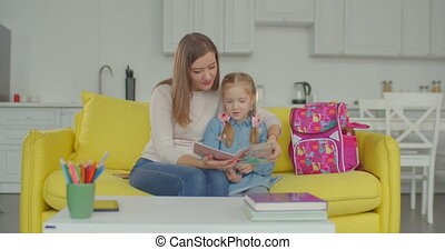 Proud mom praising schoolgirl for studying well - Loving...