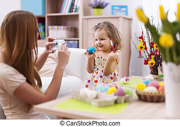 Proud mother take a picture her daughter with easter egg