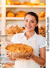 Proud of her baked goods. Beautiful young woman in apron holding basket with baked goods while standing in bakery shop