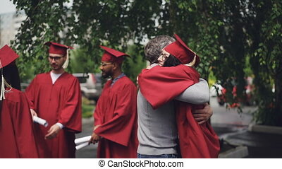 Proud parent is hugging his successful daughter graduate...