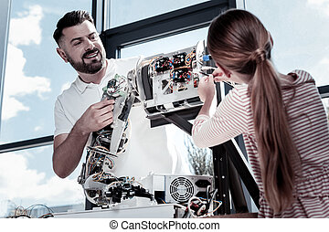 Proud teacher looking at female student working on robot