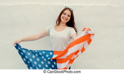 Proud woman with the American flag and wide smile. Portrait of a lovely young ginger hair woman with United State's flag waving