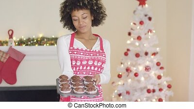 Proud young cook displaying her Christmas muffins - Proud...