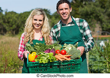 Proud young couple showing vegetables in their garden ...