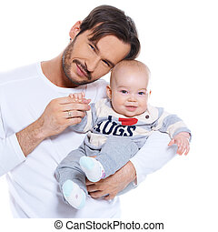 Proud young father posing with his baby cradled on his arm, both smiling happily at the camera isolated on white