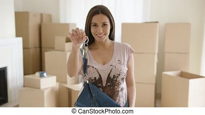 Proud young woman holding up a set of house keys as she...