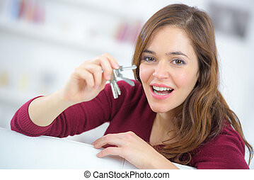 proud young woman holding up a set of house keys