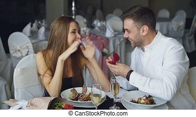 proverbe, petit ami, femme, elle., elle, restaurant, concept., engagement, baisers, relation, doigt, mariage, romantique, date, mettre, oui, proposition, anneau, séduisant
