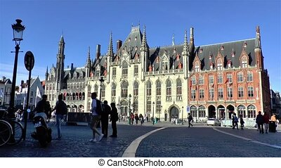 Tourists gather at the popular Markt Square in Bruges, Belgium, where the Provincial Court building stands since medieval times.