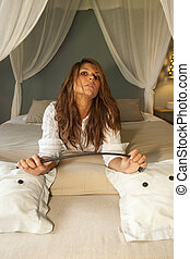 Provocative girl in bed with horsewhip looking at the camera