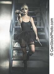 Provocative. Young blonde woman with black dress holding a gun.