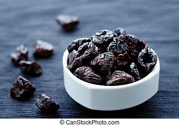 prunes in a bowl on a dark background. tinting. selective...
