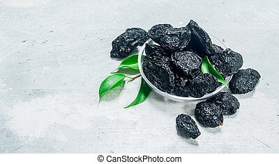 Prunes in a bowl with green leaves.